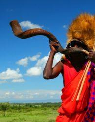 Massai-Krieger, der traditionelles Horn spielt. Afrika. Kenia. Masai Mara